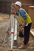 A construction worker uses a theodolite to measure triangulation angles on a building project site.