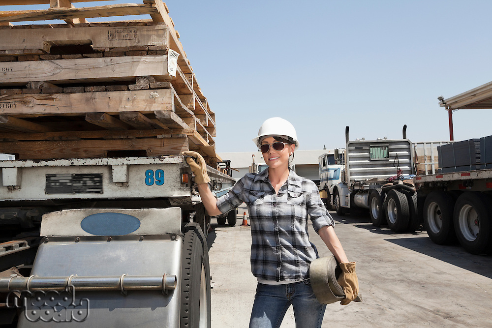 Female industrial worker standing by flatbed truck in timber yard