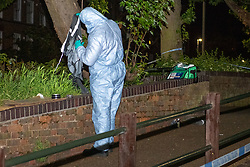 © Licensed to London News Pictures. 14/05/2020. London, UK. A forensic investigator holds up an item of clothing inside a cordon where police located two injured man. Police were called at around 1800BST on Wednesday, 13 May, to reports of a man with a knife in Lombard Road, SW11. There were also reports of a car in collision with a wall in Lombard Road. Officers attended the location and found two men injured - one had cuts to his arms and the other cuts to his legs. Officers believed the two men had been travelling in the car. Both have been taken to hospital, where their injuries are not believed to be life-threatening. Investigations at the scene led officers to Vicarage Crescent, SW11, where they found two other injured men. Both were taken to hospital with non life-threatening injuries. Photo credit: Peter Manning/LNP