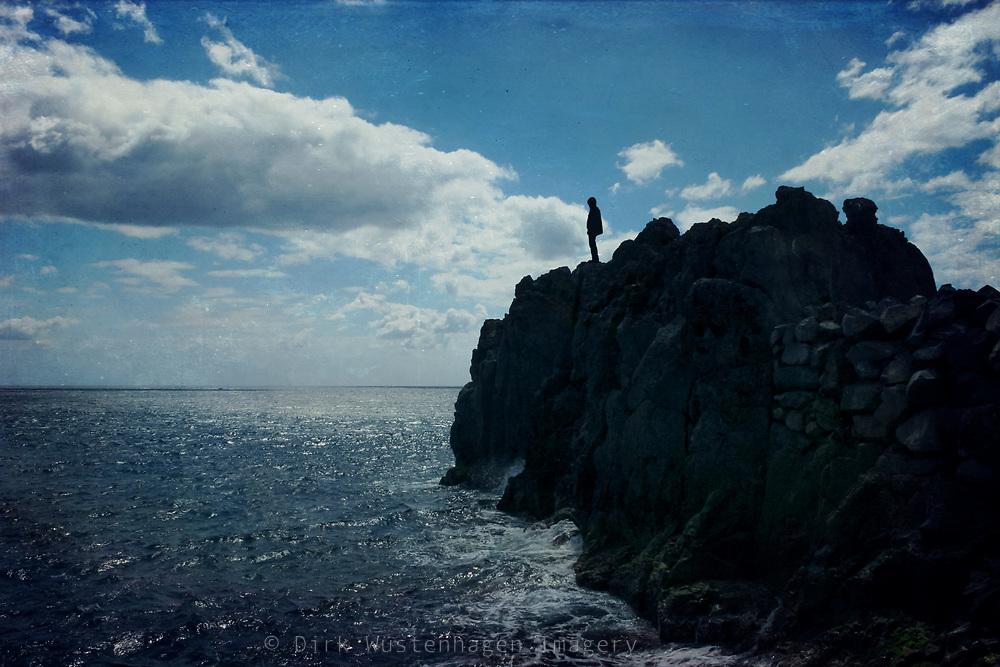 Silhouette eines Mannes auf Felsen auf den Atlantik blickend, texturierte Fotografie, Camara do Lobos, Madeira, Portugal