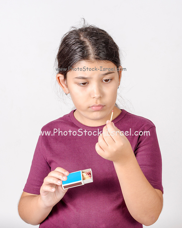 Dangerous young girl plays with matches contemplating fire and chaos