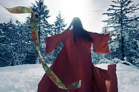 Artistic photo of an asian woman with long black hair wearing a red kimono dancing in the snow, spinning around and tossing her clothes away