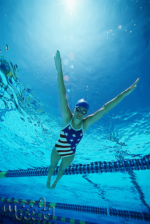 Female swimmer wearing United States swimsuit, swimming in pool