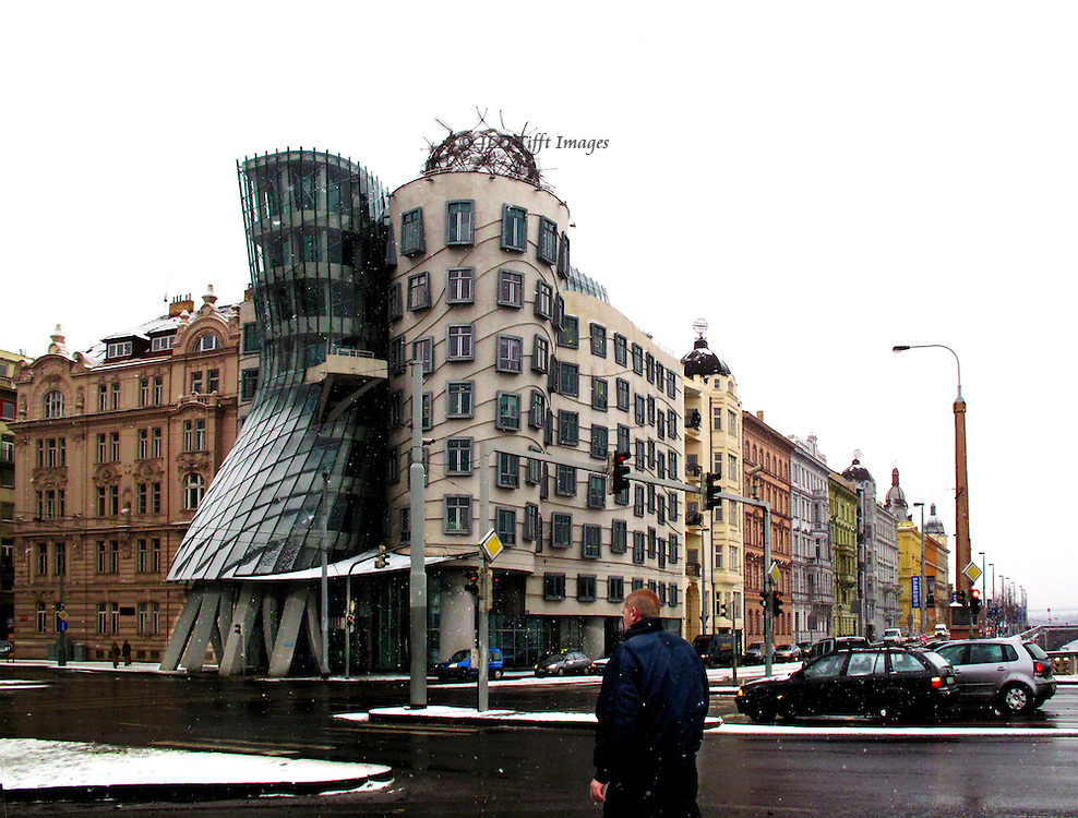 Office building designed by Frank Gehry with Vlado Milunic, built 1994-96 on a site destroyed in World War II bombing.  It is uniquely deconstructivist in style, its flamboyant modernity successfully cohabiting with the medieval buildings on either side.  Seen from across a wet street with snow on the ground.  One man, pedestrian, in the foreground.  Several parked cars in front of the building; one black sedan waiting at the crossroads traffic light.