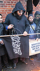 """© Licensed to London News Pictures . London , UK . MOHAMMED REZA HAQUE (known as """" Giant """" ) (wearing sunglasses) in front of a burning poppy at a Muslims Against Crusades demonstration on Exhibition Road in London , on the anniversary of Armistice Day , 11th November , in 2010 . Haque is believed to be one of five executioners featured on a recent ISIS video filmed in Syria , alongside Siddhartha Dhar (known as """" Jihaddi Sid """"). Dhar was also present at the same event on Exhibition Road in London on 11/11/2010 . Photo credit : Joel Goodman/LNP"""