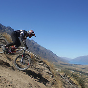Jamahl Stringer from Wellington in action during the New Zealand South Island Downhill Cup Mountain Bike series held on The Remarkables face with a stunning backdrop of the Wakatipu Basin. 150 riders took part in the two day event. Queenstown, Otago, New Zealand. 9th January 2012. Photo Tim Clayton