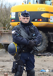 © Licensed to London News Pictures . 04/03/16 . An armed police officer stands guard on the edge of the Calais Jungle inFrance. French authorities are continuing to clear parts of the migrant camp. Photo credit : Ian Homer/LNP