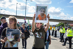London, UK. 2 September, 2019. Activists hold images of children killed by Israeli weapons in Gaza during a protest outside the Excel Centre on the first day of week-long protests against DSEI 2019, the world's largest arms fair. The first day of creative action was hosted by activists calling for a ban on arms exports to Israel and featured workshops, speakers, street theatre and dance. Israeli arms companies display weapons at DSEI marketed as 'combat-proven' following deployment against Palestinian communities.
