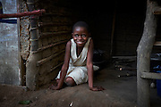 "Esperance Mulwefakadi at the family home in Kikwit, Bandundu Province, Democratic Republic of Congo on November 14, 2014. Esperance received a scholarship through the program 'VAS-Y Fille' and has been able to continue the last two years of school. From a disadvantaged family, her mother has been sick and bed ridden for many years and her father and extended family whom she lives with scrape by collecting manyok roots which they dry and sell to make a meagre living. ""I would like to continue my studies into high school if my family has the means to support me and I dream of one day becoming a nurse."" The Bana Kimono primary school has 394 students with 40 in total female students receiving a scholarship from years 5 & 6. CRS with partner Caritas and organisations International Rescue Committee and Save the Children are engaged in a education initiative focusing on assisting female students from financially disadvantaged families continuing studies in the final two years of primary school. The program 'VAS-Y Fille' or 'Go Girl!' supplies scholarships to help pay the school fees and books for students from disadvantaged families."