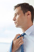 Close-up of pensive businessman loosening necktie in hotel