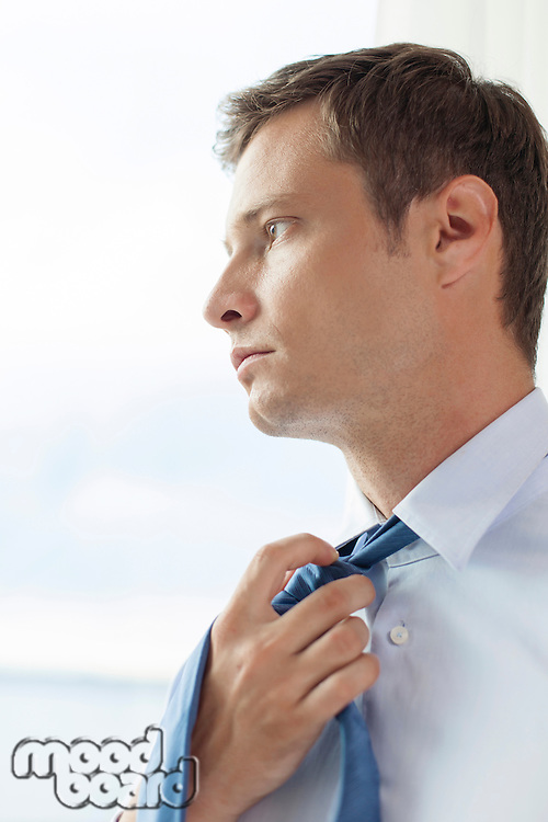 Close-up of pensive businessman loosening necktie in hotel