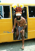 Bearded tribesman in feathered headdress arrives by modern minibus for a gathering of tribes at Mount Hagen in Papua New Guinea