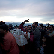 Migrants and refugees rush to collect firewood donated by locals at the Greek-Macedonian border in Idomeni, Greece. Around 13,000 migrants and refugees, mostly from the Middle East and African nations, are believe to be stranded here awaiting a chance to proceed their journey towards Germany and other northern European countries.
