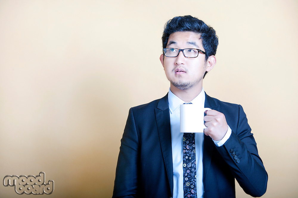 Asian businessman drinking cup of coffee