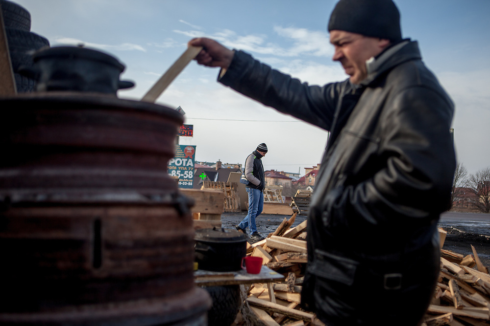 "A visitor is throwing wood into a barrel for heating the place at the barricades blocking a building supplies store named ""Epicenter"" in the city of Lviv, Ukraine."