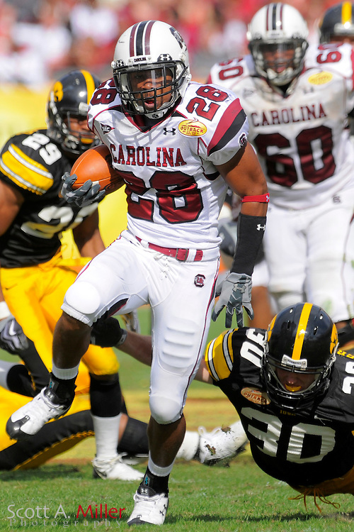 Jan 1, 2009; Tampa, FL, USA; South Carolina Gamecocks running back Eric Baker (28) high steps away from Iowa Hawkeyes cornerback Brett Greenwood (30) during the Gamecocks' 31-10 loss in the Outback Bowl at the Raymond James Stadium. ©2009 Scott A. Miller