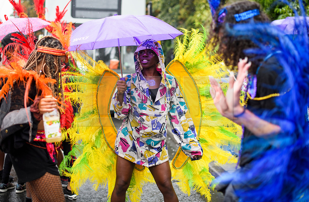 © Licensed to London News Pictures. 26/08/2018. London, UK. A carnival goer, wearing a rain coat and carrying an umbrella, makes the best of the wet and windy conditions at family day of the 2018 Notting Hill Carnival. Up to 1 million people are expected to attend this weekend's event that is one of the worlds largest street festivals. Photo credit: Ben Cawthra/LNP