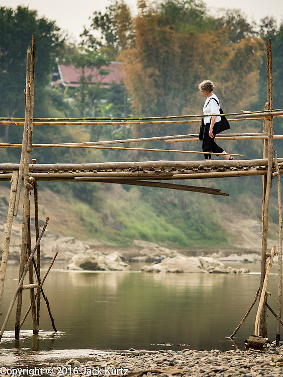"""12 MARCH 2016 - LUANG PRABANG, LAOS:  A tourist walks across a bamboo bridge spanning the Nam Khan River in Luang Prabang. Luang Prabang was named a UNESCO World Heritage Site in 1995. The move saved the city's colonial architecture but the explosion of mass tourism has taken a toll on the city's soul. According to one recent study, a small plot of land that sold for $8,000 three years ago now goes for $120,000. Many longtime residents are selling their homes and moving to small developments around the city. The old homes are then converted to guesthouses, restaurants and spas. The city is famous for the morning """"tak bat,"""" or monks' morning alms rounds. Every morning hundreds of Buddhist monks come out before dawn and walk in a silent procession through the city accepting alms from residents. Now, most of the people presenting alms to the monks are tourists, since so many Lao people have moved outside of the city center. About 50,000 people are thought to live in the Luang Prabang area, the city received more than 530,000 tourists in 2014.      PHOTO BY JACK KURTZ"""
