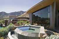 Exterior of a modern house with a small pool and mountains in the background
