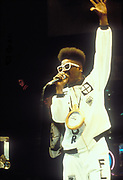 Flavour Flav from Public Enemy wearing large clock necklace and white rimmed sunglasses on mic, U.K, 1990s.