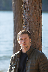 portrait of a good looking man outdoors leaning against a tree