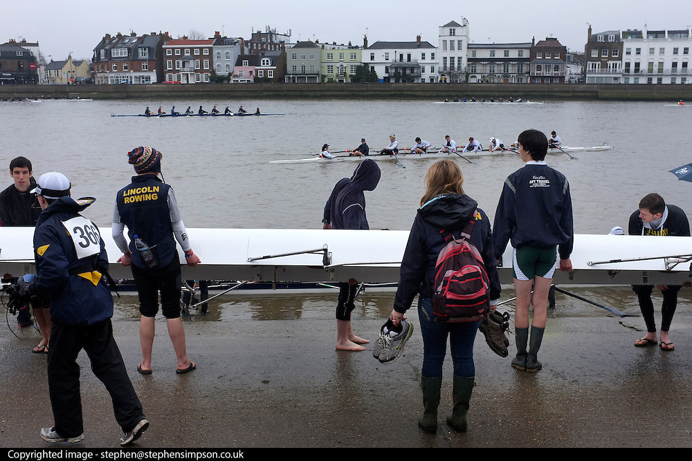 © Licensed to London News Pictures. 17/03/2012. London, UK. A rowing team from Lincoln prepare to put their boat in the water. Crews participate in the rain today,  Saturday 17th March, in The Head of the River Race which is rowed annually in March from Mortlake to Putney on the River Thames in London.  Over 400 crews of eights take part, making it one of the highest participation events in London.. Photo credit : Stephen SImpson/LNP