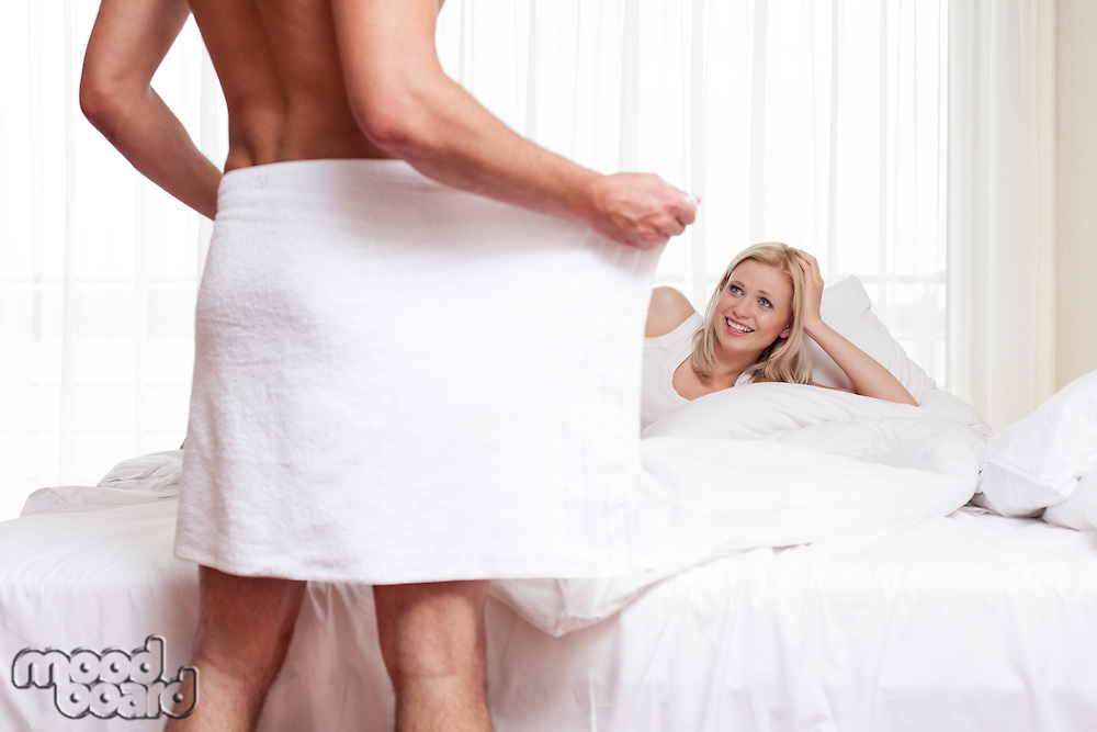 Smiling young man looking at naked man holding towel in bedroom