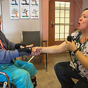 "MANASSAS, VA - NOV21:  Norma Felter sings ""Hey Jude"" with activity aide Tina Burhans-Robinson, during karaoke at Birmingham Green, an elder care residence in Manassas, VA, November 21, 2014. With the U.S. population aging and Alzheimer's more widespread, science is looking for ways to slow or delay the onset of dementia in aging Americans. Among the approaches is trying to determine whether art, music and dance or movement can also alleviate the problems attendant with dementia. The federal government is funding a study at Birmingham Green with George Mason University to see whether there is a scientific basis to believe that art is actually medically beneficial. (Photo by Evelyn Hockstein/For The Washington Post)"