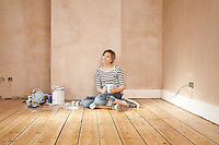 Woman sitting on floor of unrenovated room holding coffee mug