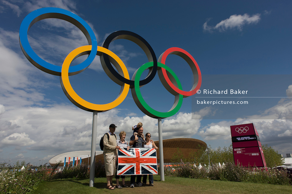 British spectators pose for family photos beneath giant Olympic rings located on a hill in the Olympic Park during the London 2012 Olympics. This land was transformed to become a 2.5 Sq Km sporting complex, once industrial businesses and now the venue of eight venues including the main arena, Aquatics Centre and Velodrome plus the athletes' Olympic Village. After the Olympics, the park is to be known as Queen Elizabeth Olympic Park.