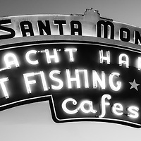 "Santa Monica Pier sign panoramic black and white photo. Panoramic photo ratio is 1:3. The famous Santa Monica pier neon sign says ""Santa Monica Yacht Harbor Sport Fishing Boating Cafes"". Santa Monica Pier is a landmark located in Los Angeles County Southern California and has an amusement park with a ferris wheel, roller coaster, restaurants, and other attractions."