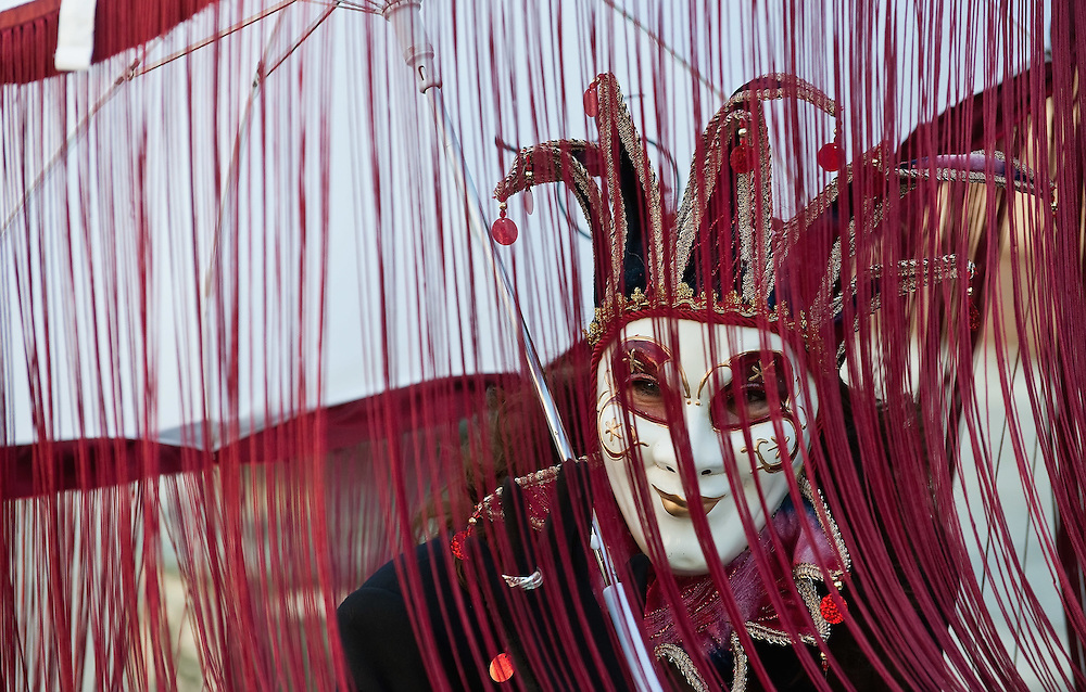 VENICE, ITALY - FEBRUARY 19:  A member of the public wearing a red costume and a Venetian masks poses in St Mark Square ahead of the opening ceremony on February 19, 2011 in Venice, Italy. The fountain pouring wine features today during the Gran brindisi a Venezia or Grand Toast in Venice, the opening ceremony of this year Carnival .
