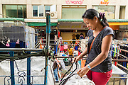 06 JUNE 2013 - BANGKOK, THAILAND:     A blue jeans vendor folds jeans in her market stall in Bobae Market in Bangkok. Bobae Market is a 30 year old market famous for fashion wholesale and is now very popular with exporters from around the world. Bobae Tower is next to the market and  advertises itself as having 1,300 stalls under one roof and claims to be the largest garment wholesale center in Thailand.       PHOTO BY JACK KURTZ