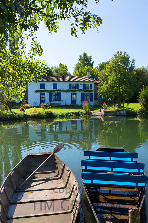 Rowing boats and house by River La Sevre-Niortaise in Coulon in Marais Poitrevin region, Grand Site de France
