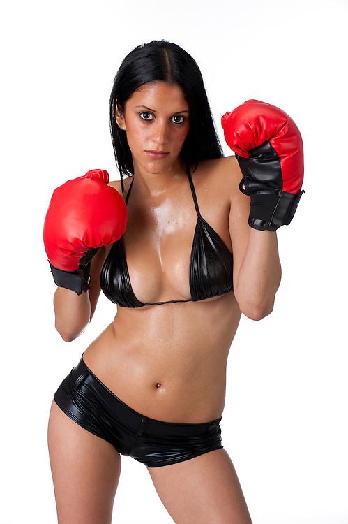 Young latin woman in bikini training with boxing gloves and sweaty.