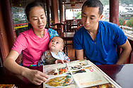 An adult woman holding a baby and her husband order breakfast at a restaurant in Yangshuo, China (Model Released, Sean, Rachel and Tintin Ouyang).
