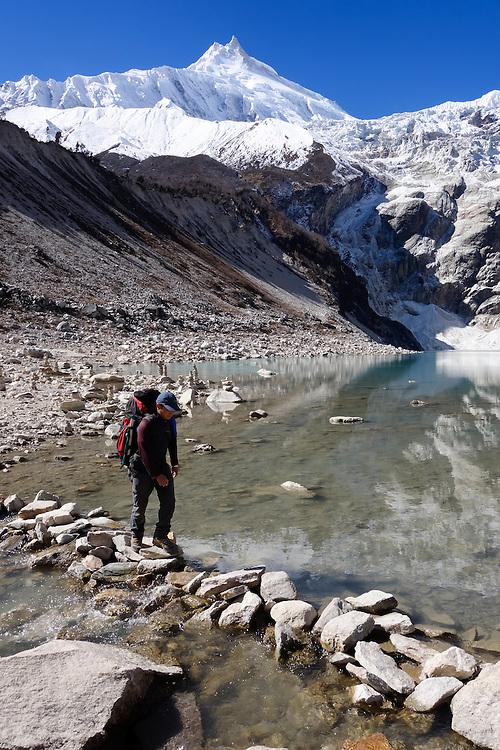 Trekker crossing the outlet of Birendra Tal (Lake Birendra), Nepal.  Manaslu peak is in the background.