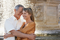 Middle-aged couple hugging by fountain Rome Italy close up