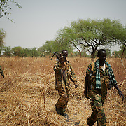April 24, 2012 - Lalop, South Sudan: SPLA soldiers walks by a field, recently bombed by Sudan troops, in the outskirts of a newly established military base in the village o Lalop, 50 kilometers north of Bentiu...South Sudan and their northern neighbors, Sudan, have in the past two weeks been involved in heavily clashes over border disputes. Bentiu and neighboring villages have been under constant bombardment by the troops os Karthoum , who established their positions around 10 kilometers into South Sudan's territory. The international community is concerned about the possibility of a full on war between the two countries. (Paulo Nunes dos Santos/Polaris)