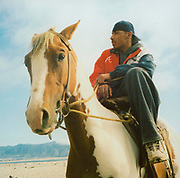 Teenager sitting on a horse in the desert USA