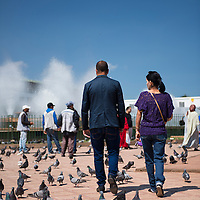 Moroccans walking by the Pigeon Fountain in Place Mohammed V in Casablanca, Morocco.