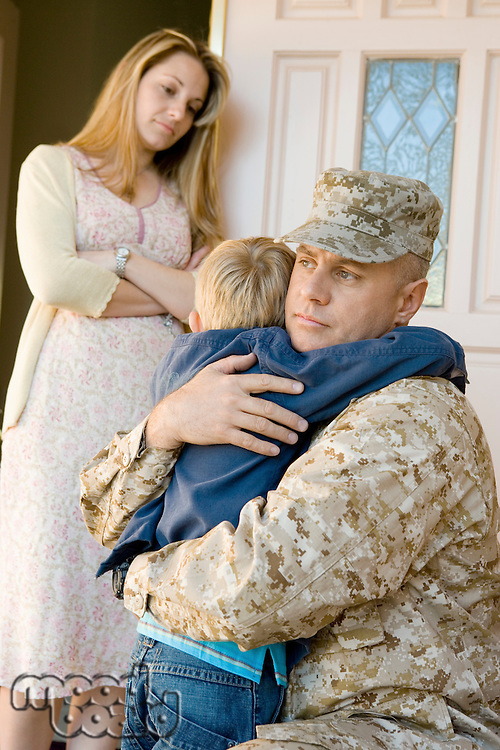 Military father embracing son (5-6) outside home wife watching