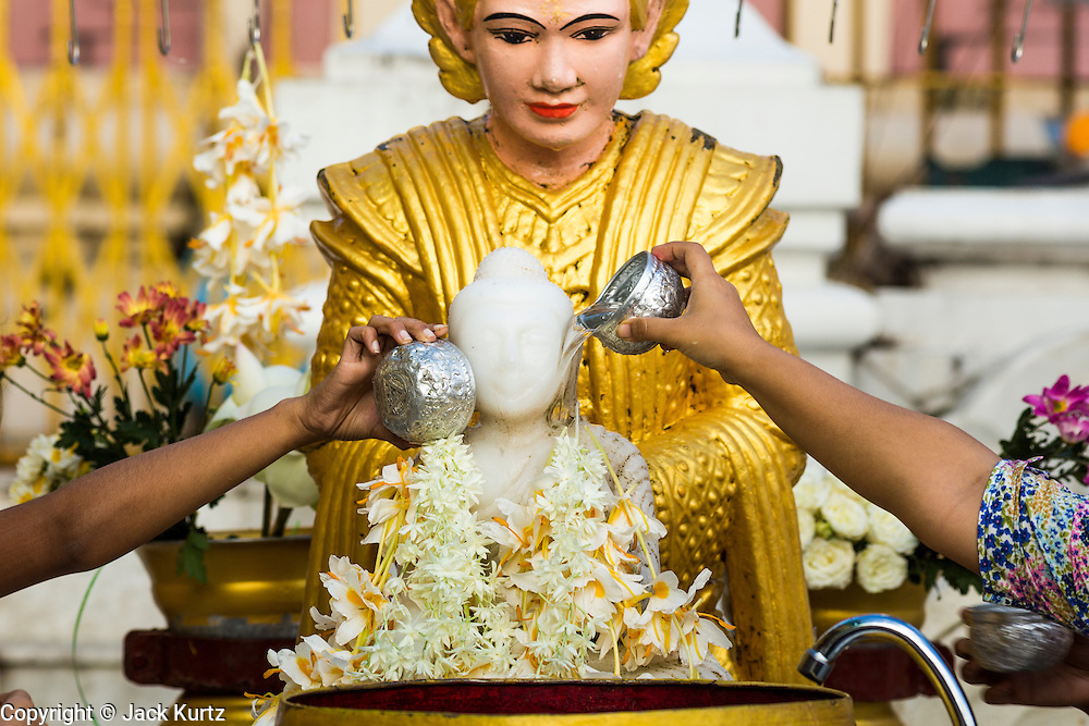 15 JUNE 2013 - YANGON, MYANMAR: People bathe a statue of the Buddha to make merit at Shwedagon Pagoda. Shwedagon Pagoda is officially known as Shwedagon Zedi Daw and is also called the Great Dagon Pagoda or the Golden Pagoda. It is a 99 meter (325 ft) tall pagoda and stupa located in Yangon, Burma. The pagoda lies to the west of on Singuttara Hill, and dominates the skyline of the city. It is the most sacred Buddhist pagoda in Myanmar and contains relics of the past four Buddhas enshrined: the staff of Kakusandha, the water filter of Koṇāgamana, a piece of the robe of Kassapa and eight strands of hair from Gautama, the historical Buddha. Burmese believe the pagoda was established as early ca 540BC, but archaeological suggests it was built between the 6th and 10th centuries. The pagoda has been renovated numerous times through the centuries. Millions of Burmese and tens of thousands of tourists visit the pagoda every year, which is the most visited site in Yangon. PHOTO BY JACK KURTZ