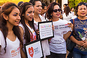 "12 JANUARY 2014 - BANGKOK, THAILAND:  Women hold up signs for Thai democracy during a candlelight vigil at Thammasat University in Bangkok. About 500 people from all walks of Thai life came to a candlelight vigil at Thammasat University. They prayed for a peaceful resolution to the political conflict in Thailand. They finished the vigil by singing the John Lennon song ""Imagine."" Anti-government protestors are expected ""Shutdown Bangkok"" Monday. There were reports Sunday evening that some intersections were already being blocked.      PHOTO BY JACK KURTZ"