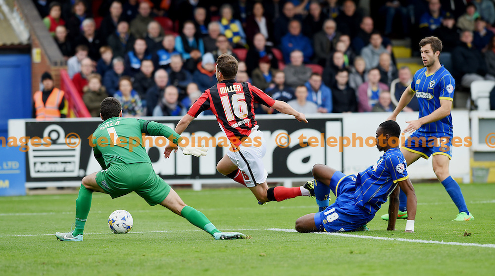 Shaun Miller of Morecambe is brought down by Wimbledon's Semi Ajayi for a penalty in the first half during the Sky Bet League 2 match between AFC Wimbledon and Morecambe at the Cherry Red Records Stadium in Kingston. October 17, 2015.<br /> Simon  Dack / Telephoto Images<br /> +44 7967 642437