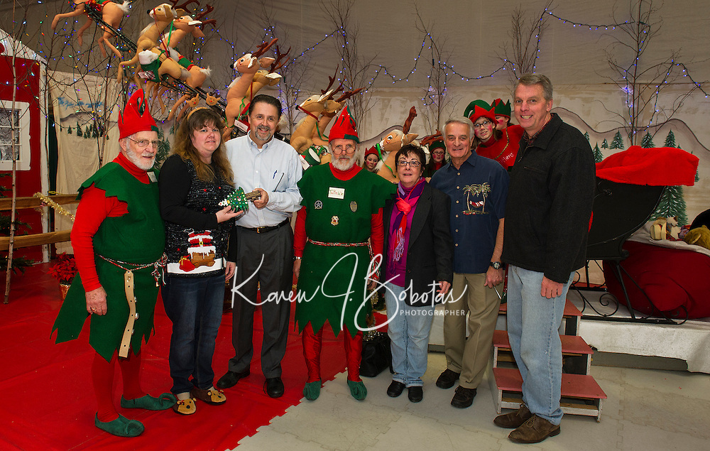 """""""Mayor"""" Renee McVey receives the key to Christmas Village from Laconia Mayor Ed Engler and city officials during opening night of Christmas Village at the Laconia Community Center.  (l-r) Tinsel (Ernie Bolduc), Renee McVey, Mayor Ed Engler, Twinkle (Armand Bolduc), Ava Doyle, Bob Hamel and Scott Myers)  (Karen Bobotas/for the Laconia Daily Sun)"""