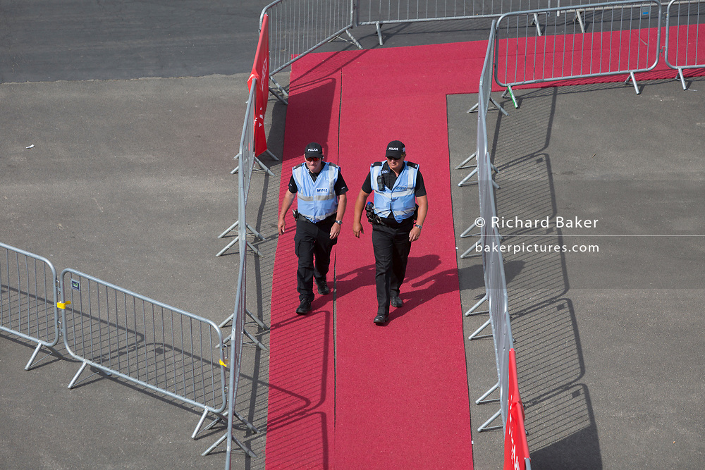 Police officers patrol a red carpet at the Leonardo (formerly Finmeccanica) exhibition stand at the Farnborough Airshow, on 16th July 2018, in Farnborough, England. (Photo by Richard Baker / In Pictures via Getty Images)