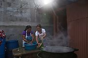 Dora Pereira (left), 38, and Vilma Tovar, 39, both from El Mozote, prepare food to sell during the commemorations of the 35th anniversary of the Massacre at El Mozote and surrounding villages. Dora and Vilma are survivors who were both displaced, living in Joateca and Honduras, respectively, for numerous years before returning to El Mozote. The massacre at El Mozote is one of six mass killings that took place in villages within the municipality of Meanguera from Dec. 11-13, 1981, by the US-trained Atlacatl Battalion of the Salvadorian Armed Forces, left over 900 civilian victims and are known collectively as the Massacre at El Mozote and surrounding villages. Earlier in 2016, an amnesty law signed after the 1992 Peace Accords that prevented war crimes from being investigated and tried was lifted by El Salvador's Supreme Court, allowing cases like El Mozote to proceed legally against its perpetrators. El Mozote, Meanguera, Morazan, El Salvador. December 10, 2016.