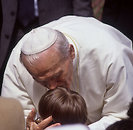 Pope John Paul II <cq> kisses the forehead of a child during his visit to the Carmel Mission in Carmel, CA, September 17, 1987.  The Pope was on an 8-city tour of the USA which began in Miami and ended in Detroit and included three stops in California (L.A., Carmel and San Francisco).
