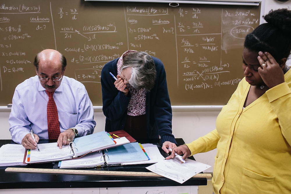 Dr. Daryao Khatri, a professor at University of Washington DC, helps Elizabeth Fogler, center, and Dana Sledge, right, with physics equations during class on Thursday, April 9, 2014. Dr. Khatri uses a variety of different methods to teach physics to students, including forgoing the standard textbook and instead giving students binders full of his lessons.